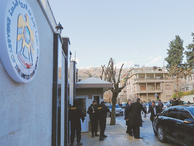 DAMASCUS: Security guards stand in front of the UAE embassy during its reopening in the Syrian capital on Thursday.—Reuters