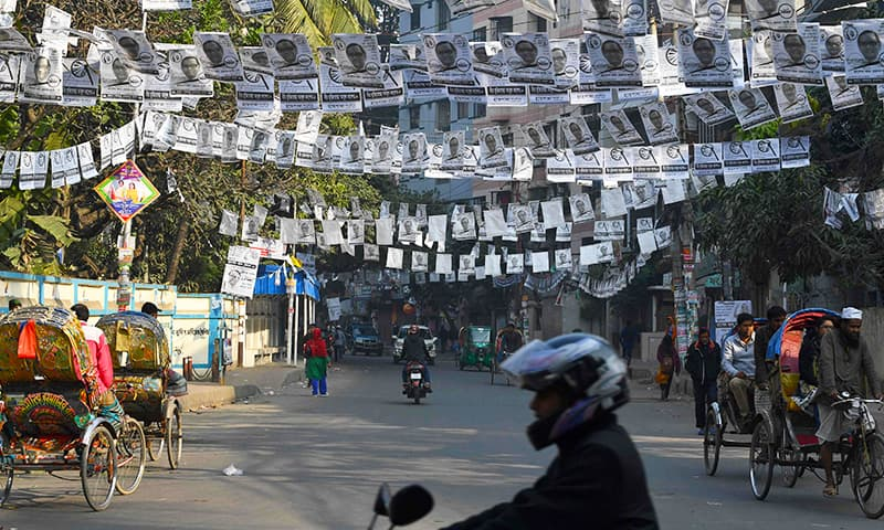 Bangladeshi people go about a street adorned with election posters in Dhaka ahead of the Dec 30 general election. — AFP
