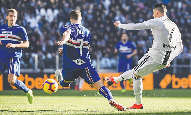 TURIN: Juventus' Cristiano Ronaldo (R) shoots to score past Jacopo Sala of Sampdoria during their Serie A match at the Juventus Stadium on Saturday. — AFP