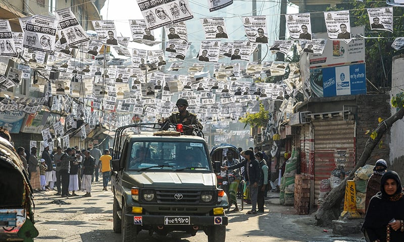 Bangladeshi army personnel drive a military vehicle through a street adorned with election posters near a polling station in Dhaka. — AFP