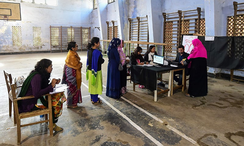 A Bangladeshi voter (r) interacts with the polling personnel as others wait in line to cast their vote at a polling station located in a gymnasium in Dhaka. — AFP