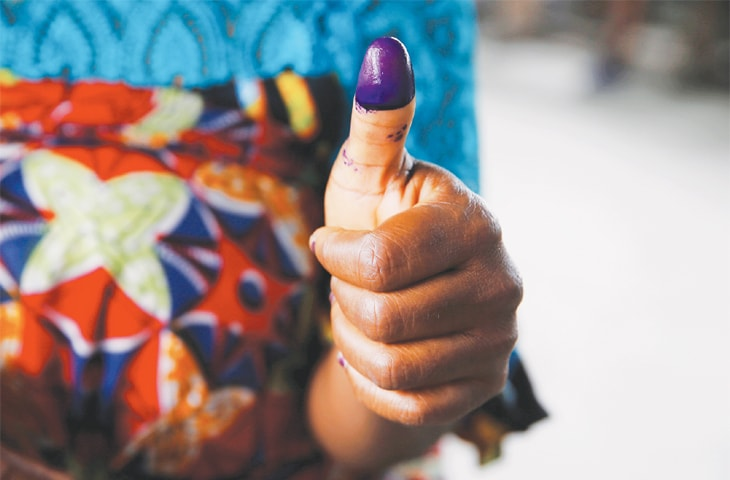Kinshasa: A woman displays ink on her finger after voting at a polling station on Sunday.—Reuters