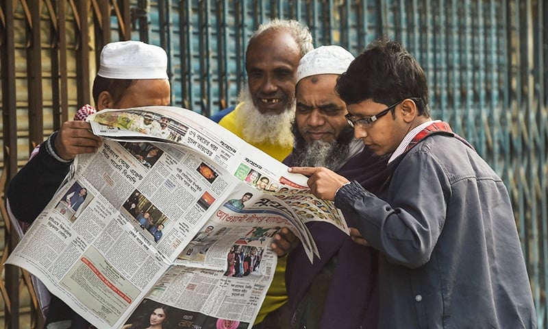 Bangladeshi people read a newspaper carrying headlines of the general election results in Dhaka on December 31. ─ AFP