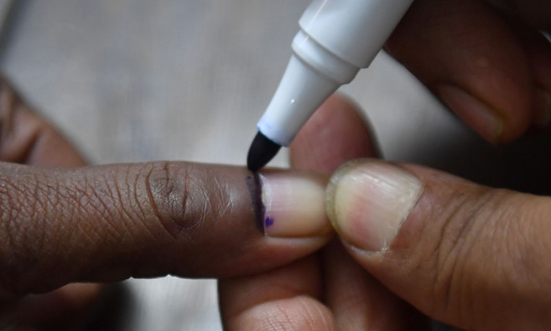 A Bangladeshi election official marks the finger of a voter at a polling station in Dhaka. ─ AFP