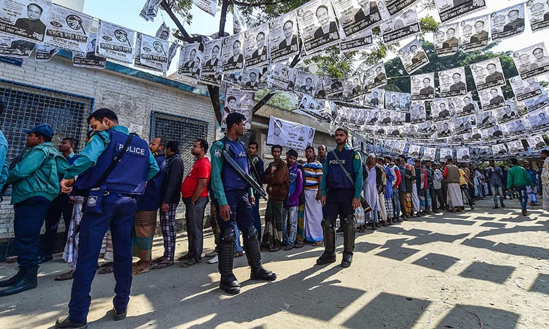 Bangladeshi voters wait in line outside a polling station while security police officials watch over in Dhaka. ─ AFP
