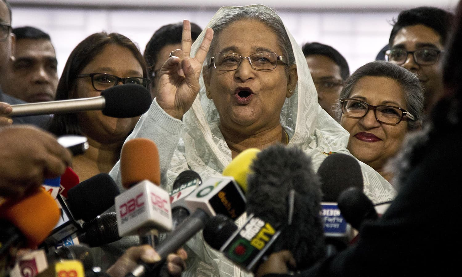 Bangladesh Prime Minister Sheikh Hasina flashes a victory sign as she speaks to the media persons after casting her vote in Dhaka. ─ AP