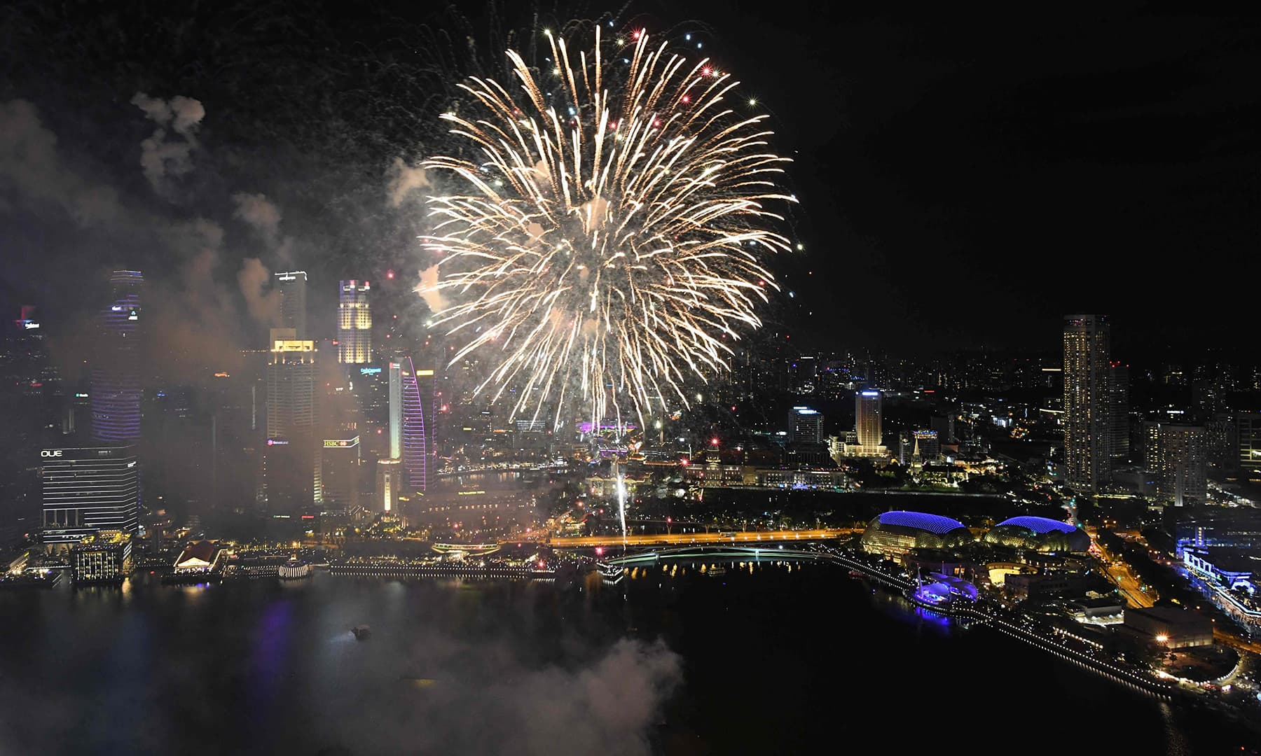 Fireworks burst over the water of Marina Bay during the eve of the New Year before the main countdown celebration in Singapore. — AFP