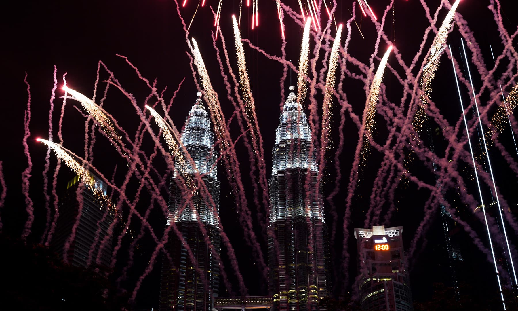 Fireworks explode in front of Malaysia's landmark building, the Petronas Twin Towers, during the New Year's celebration in Kuala Lumpur, Malaysia. — AP