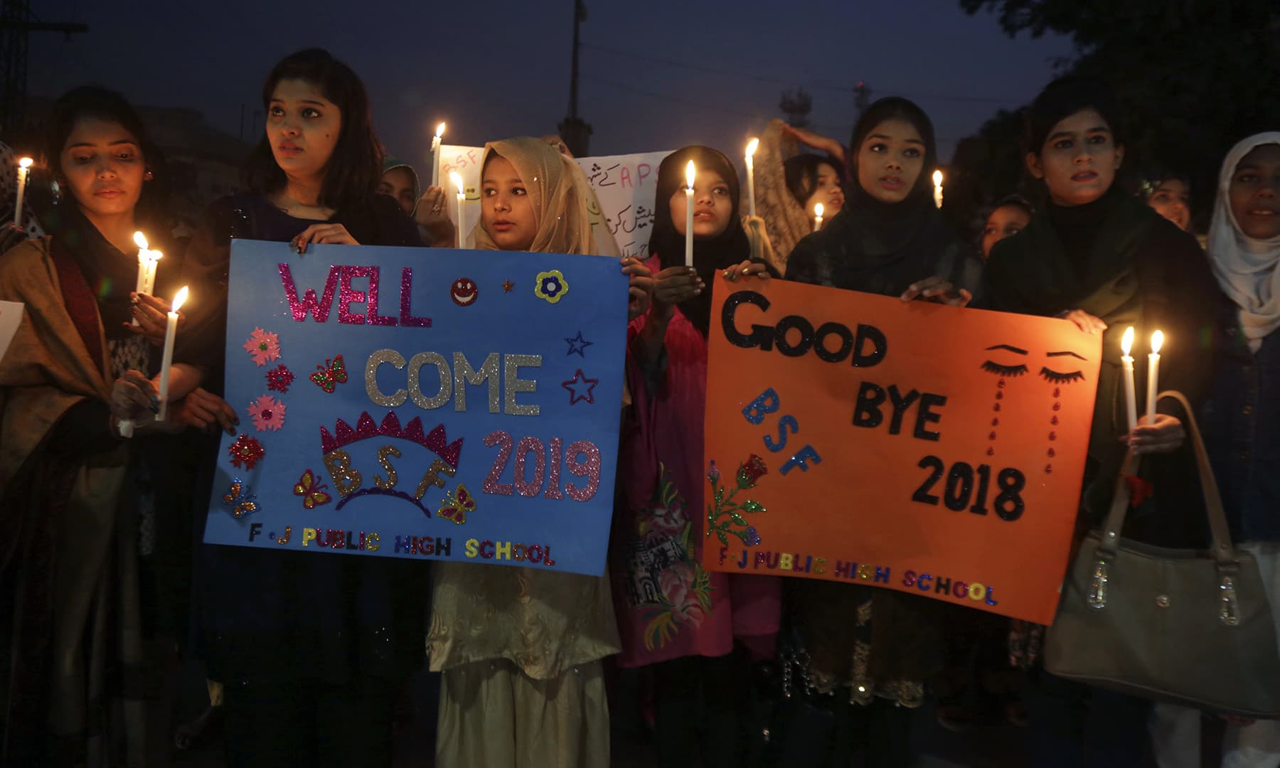 High school students hold candles to welcome a new year in Lahore on Monday. — AP