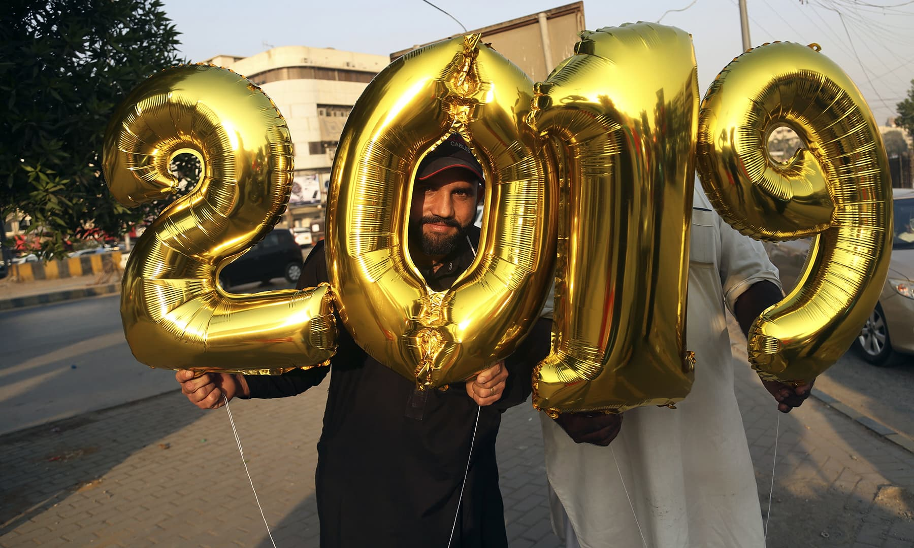 Vendors sell balloons on New Year's Eve in Karachi on Monday. — AP
