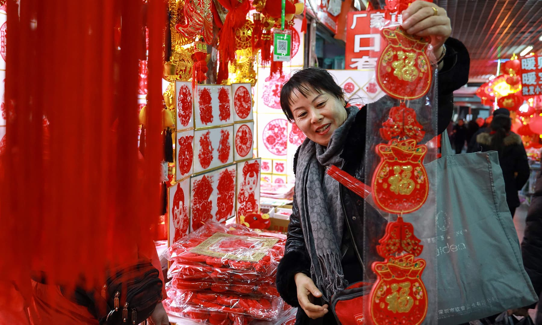 A customer buys New Year decorations at a market ahead of New Year's day in Shenyang in China's northeastern Liaoning province. — AFP