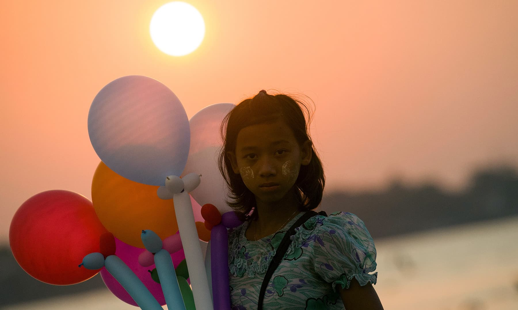 A street vendor waits for customers during the last sunset of the year in Yangon, Myanmar on December 31. — AFP