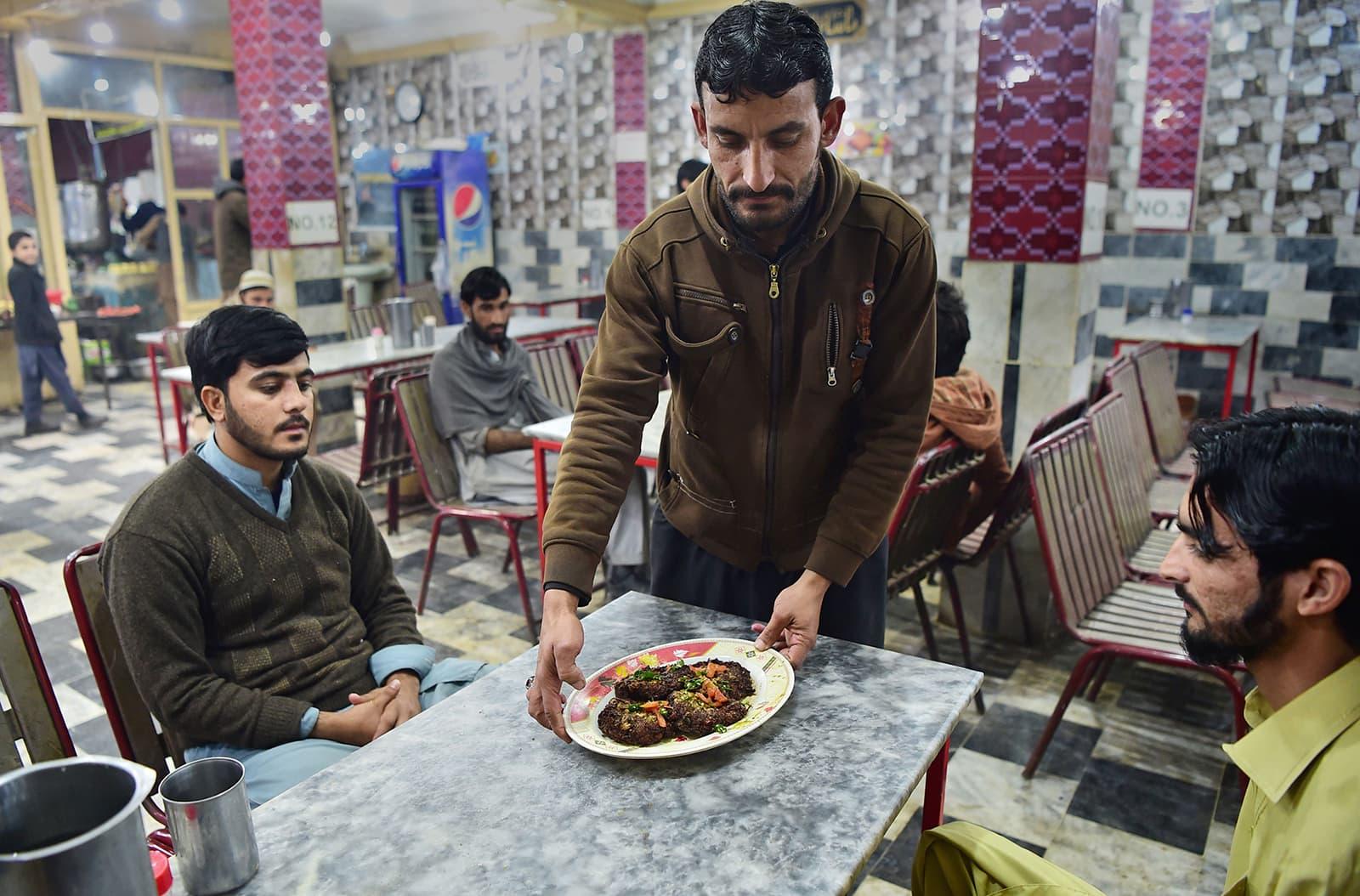 A man serves customers a plate of kebabs at the Tory Kebab House in Namak Mandi in Peshawar. — AFP