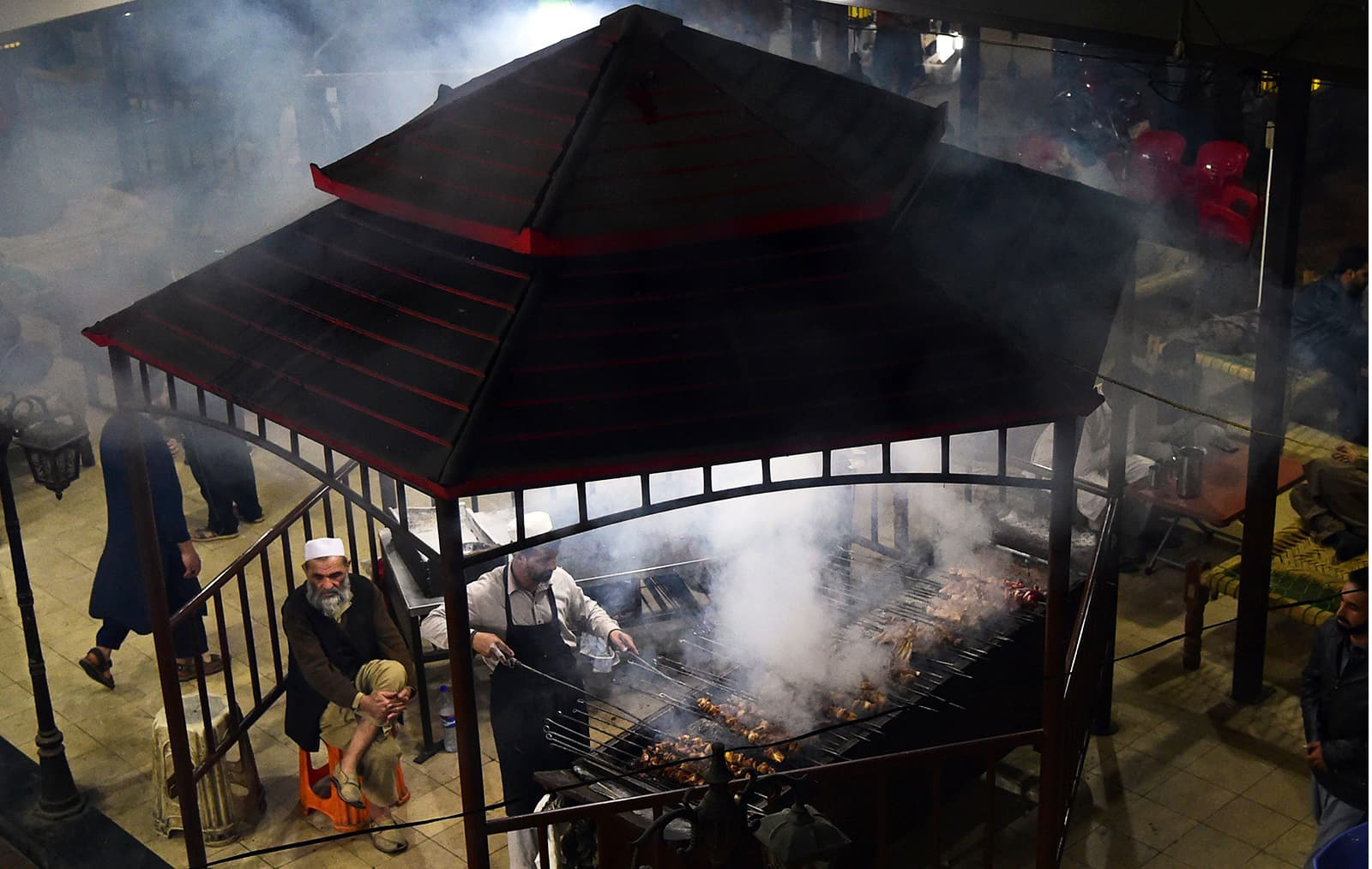 A man cooks grilled meat on a barbeque at the Charsi Tikka restaurant in Namak Mandi in Peshawar. — AFP