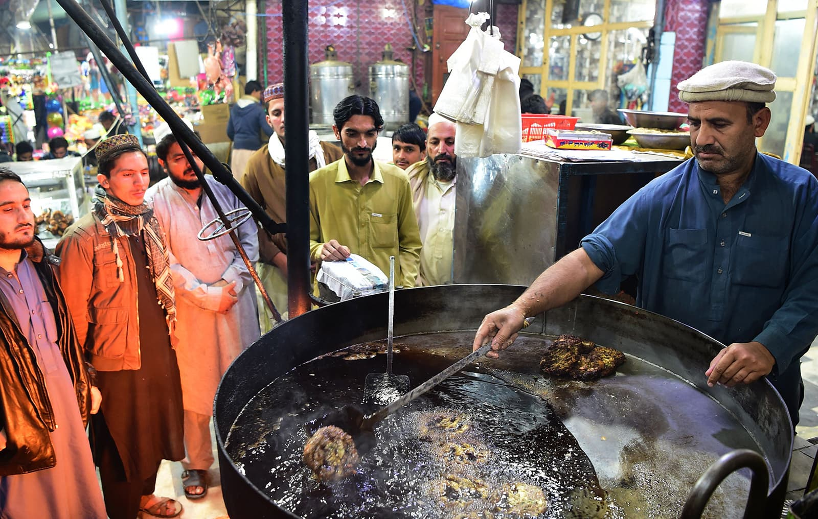 A cook grills kebabs while customers look on at the Tory Kebab House in Namak Mandi in Peshawar. — AFP