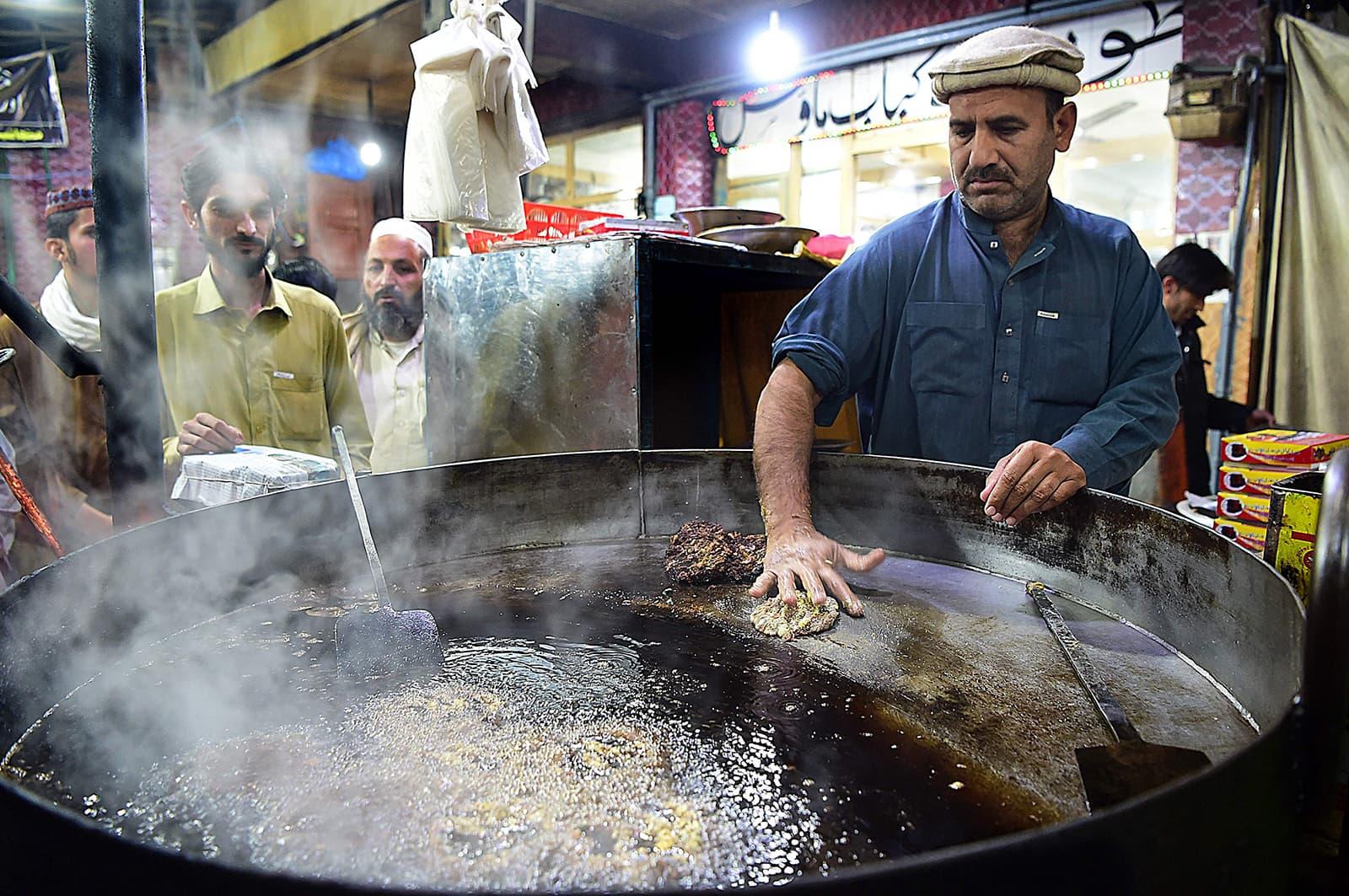 A cook fries kebabs as customers gather around at the Tory Kebab House in Namak Mandi in Peshawar. — AFP