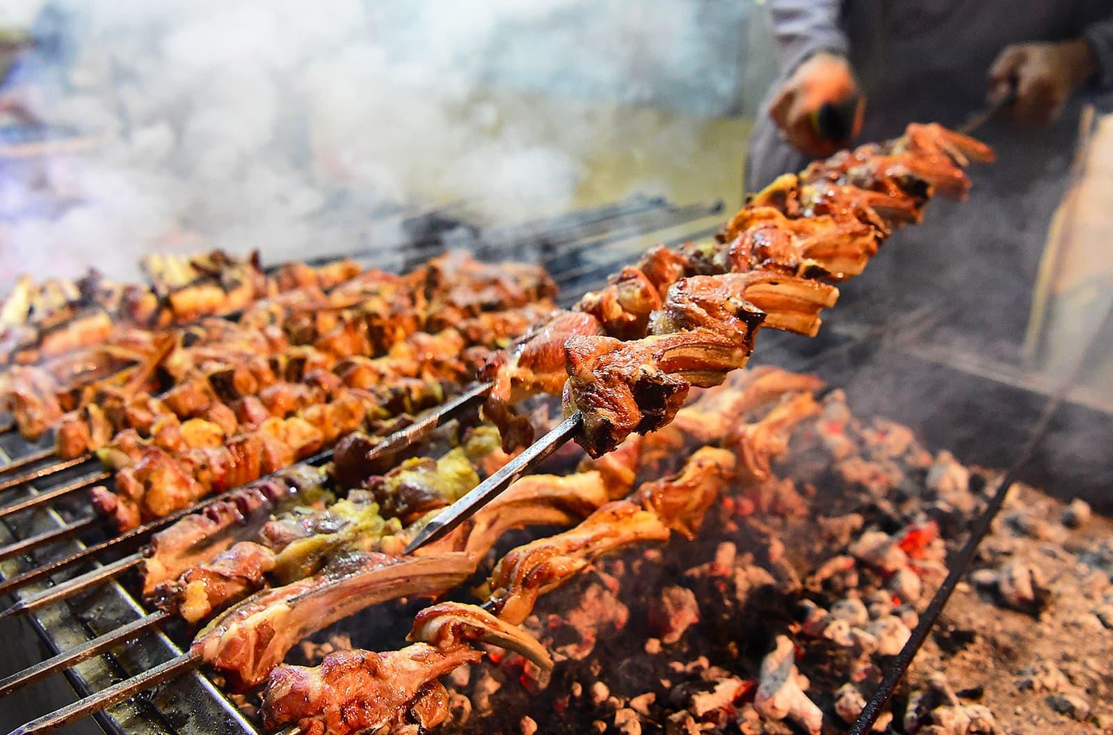 A Pakistani man cooks grilled meat at the Charsi Tikka restaurant in Namak Mandi in Peshawar. — AFP
