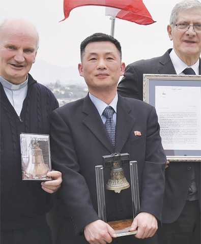 """FILE photo of North Korea's acting ambassador to Italy Jo Song Gil (centre) holding a model of """"Bell of Peace of Rovereto"""" during a cultural event in San Pietro di Feletto, northern Italy.—AP"""