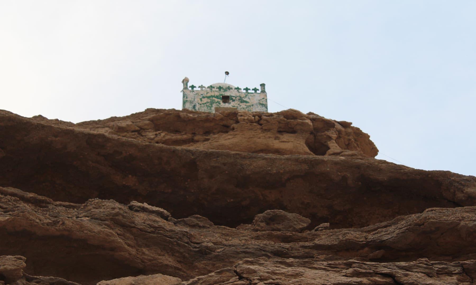 چٹان پر ایک مسجد یا مزار موجود ہے—تصویر اختر حفیظ