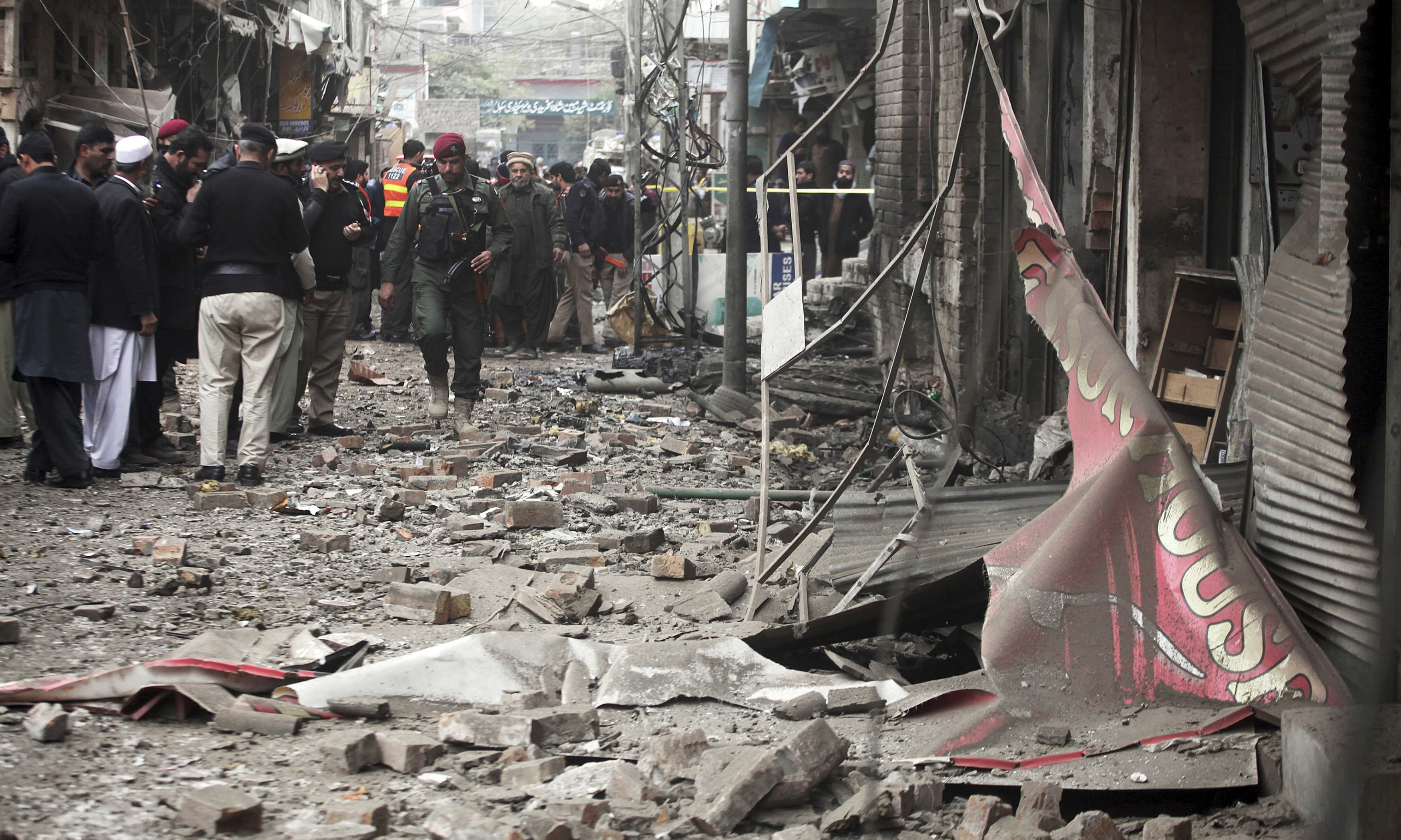 Rescue workers gather at the site of bomb blast in Peshawar. —AP