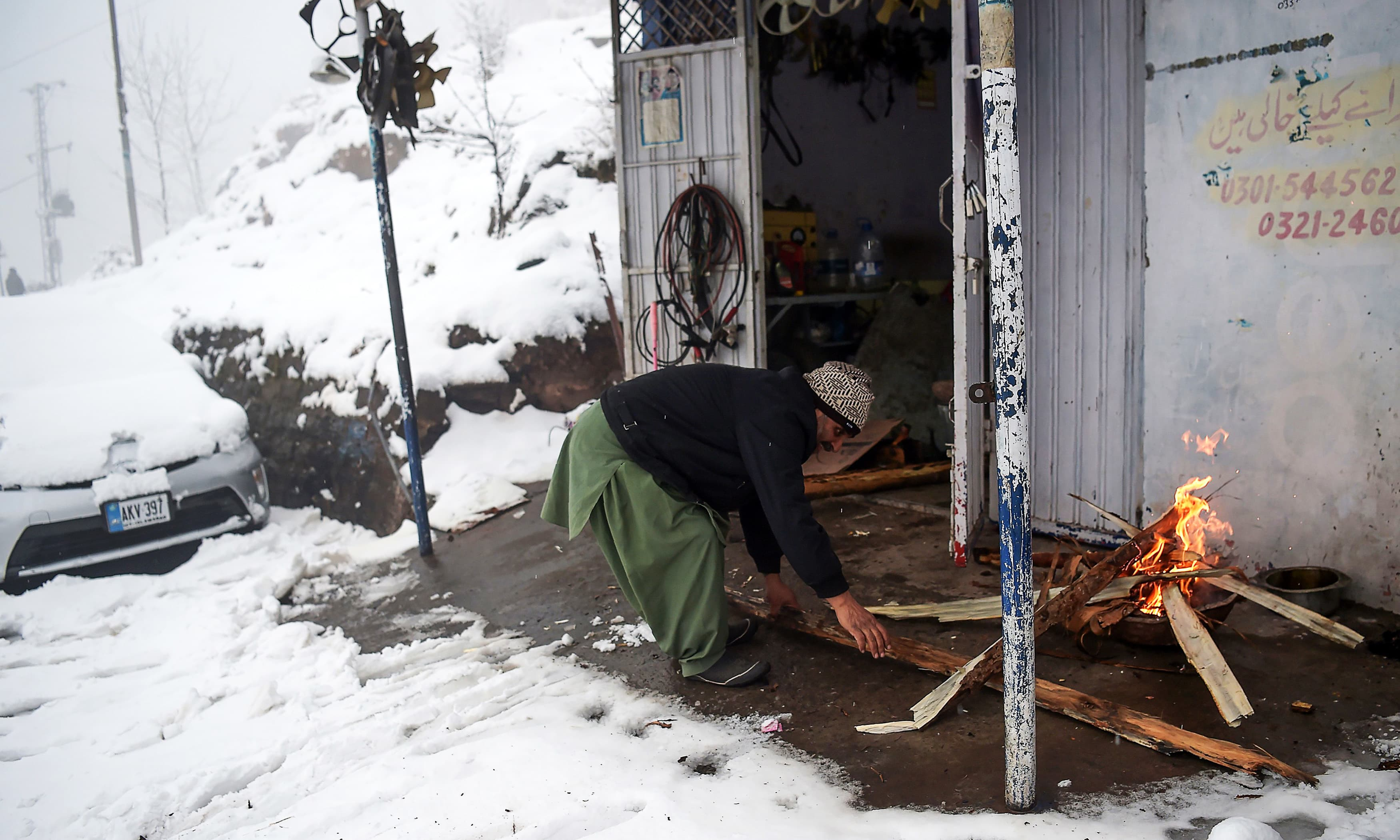 A man lights firewood outside his workshop during snowfall in Murree. —AFP