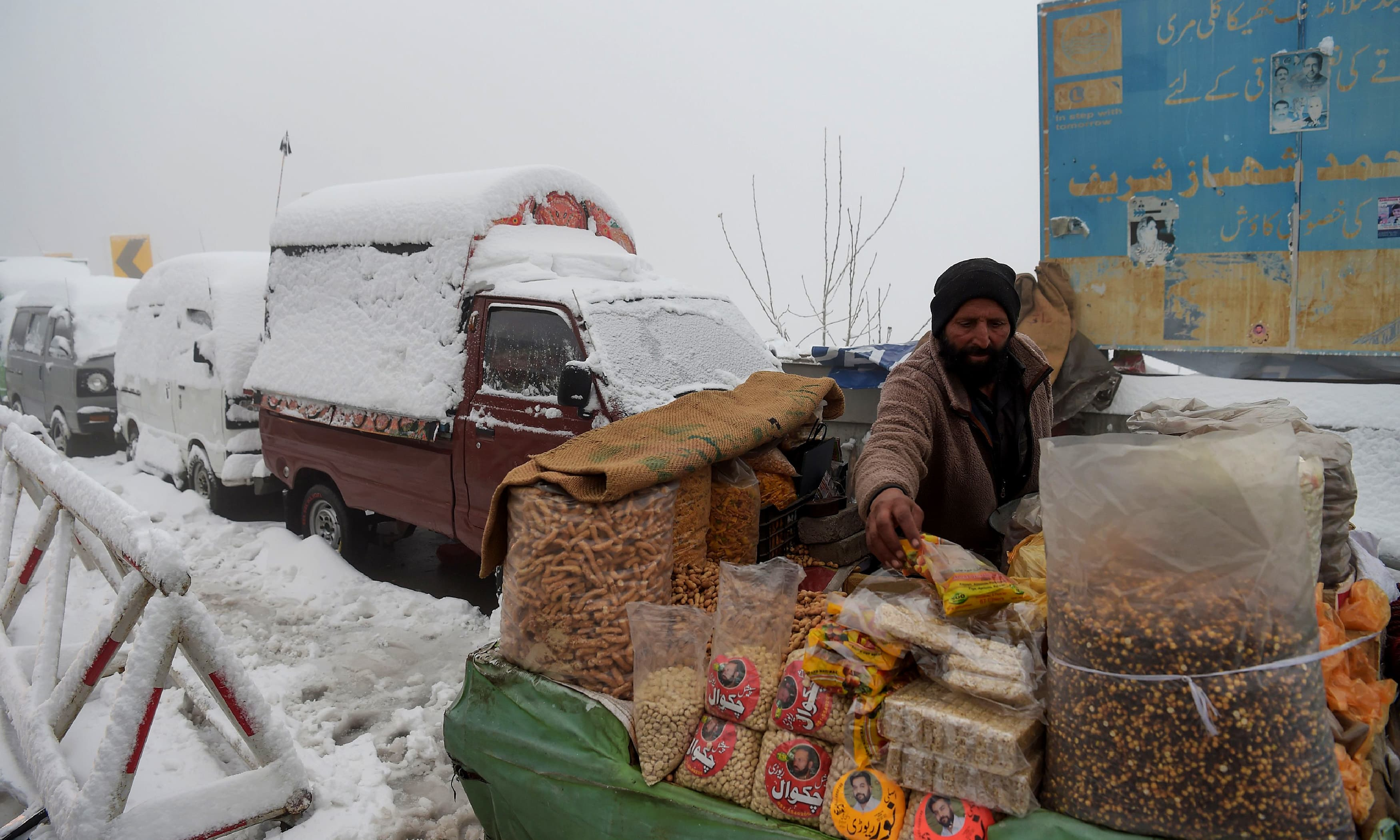 A vendor arranges his stall near vehicles covered with snow during snowfall in Murree. —AFP
