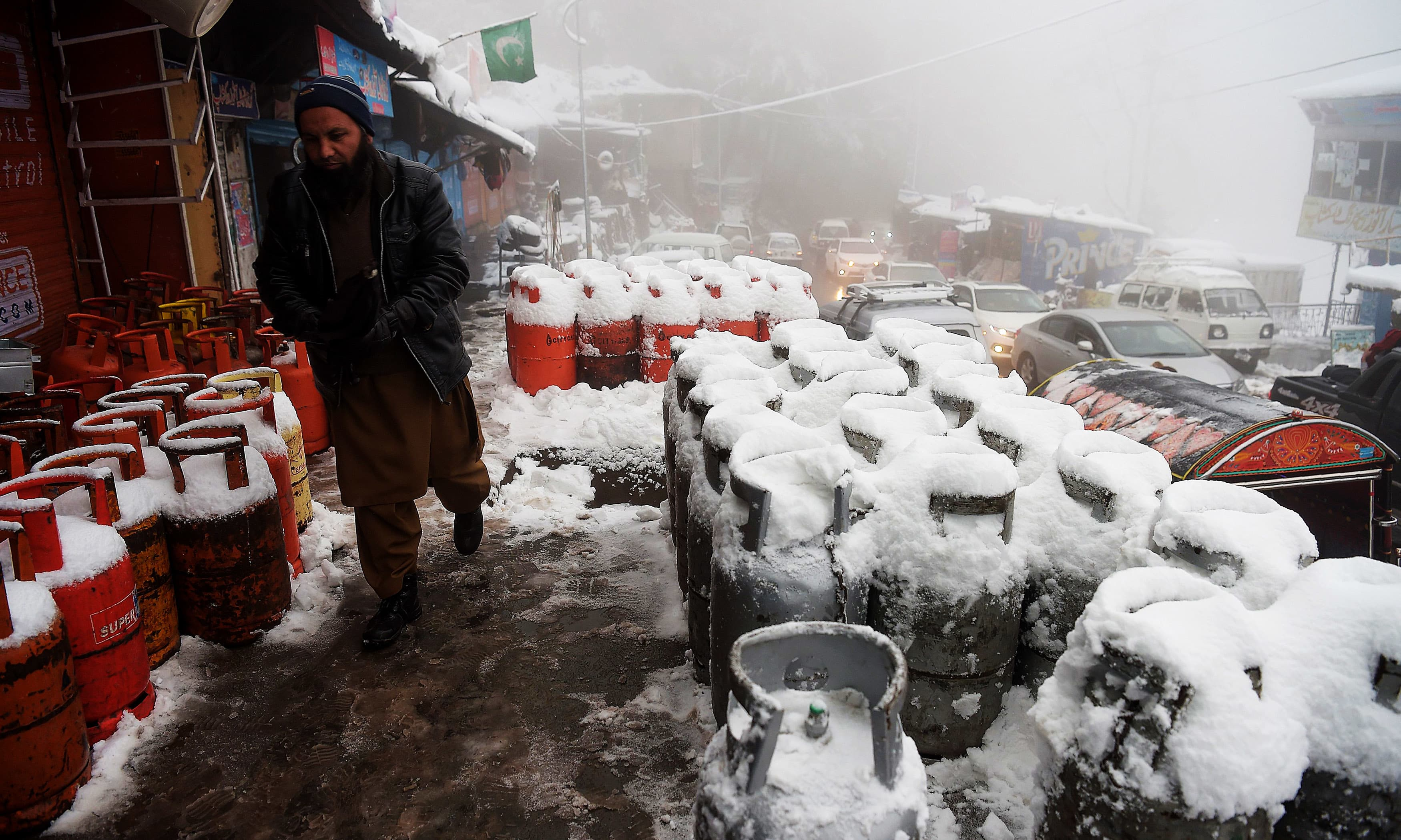A man walks past gas cylinders covered with snow in Murree. —AFP