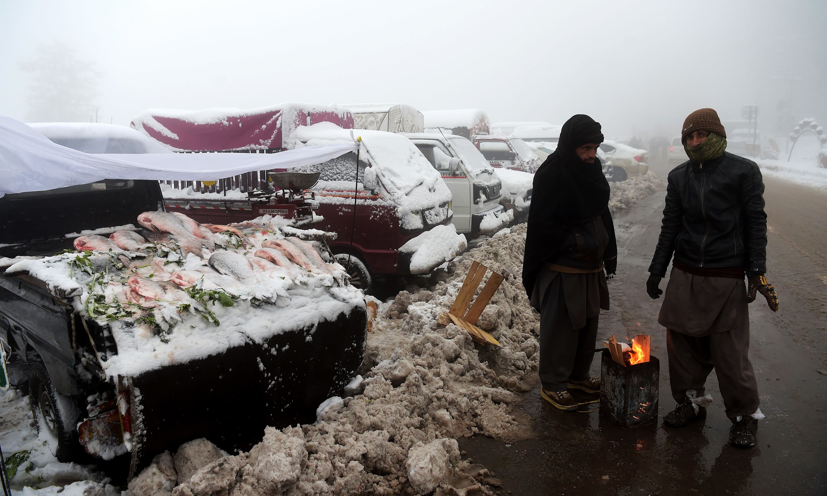 Vendors heat up around a fire next to their fish stall during snowfall in Murree. —AFP