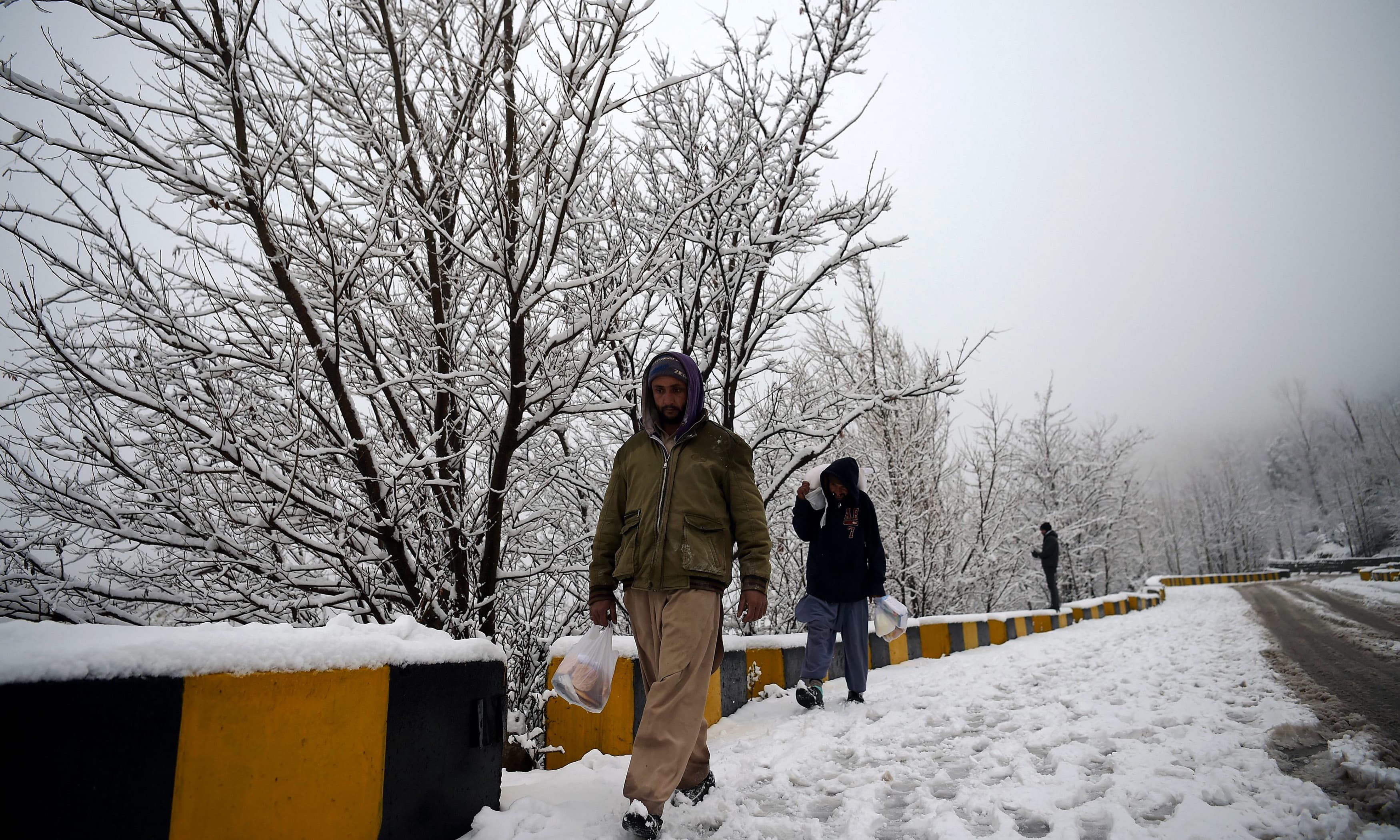 Residents walk during a snowfall in Murree. —AFP