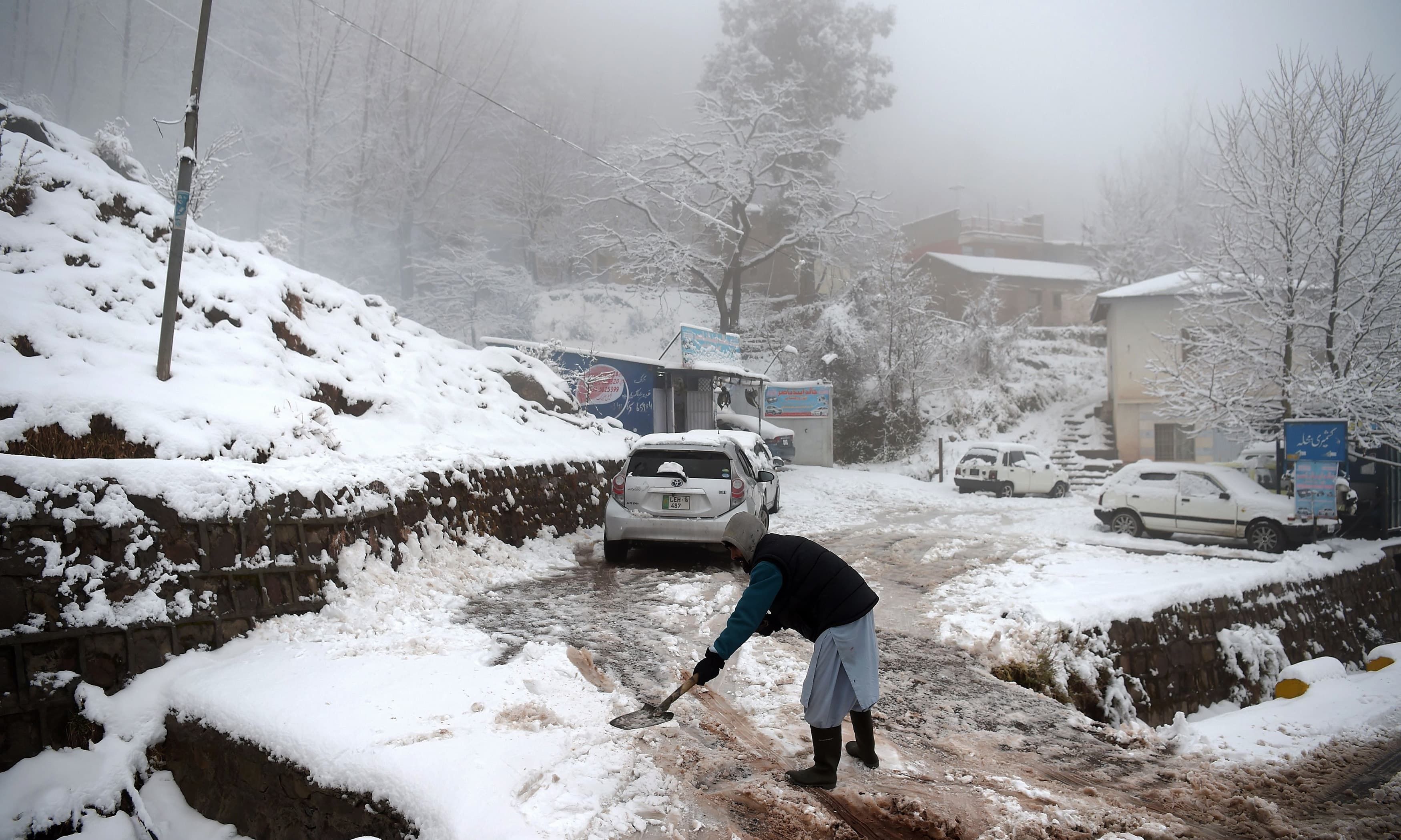 A man removes snow beside his shop during snowfall in Murree. —AFP
