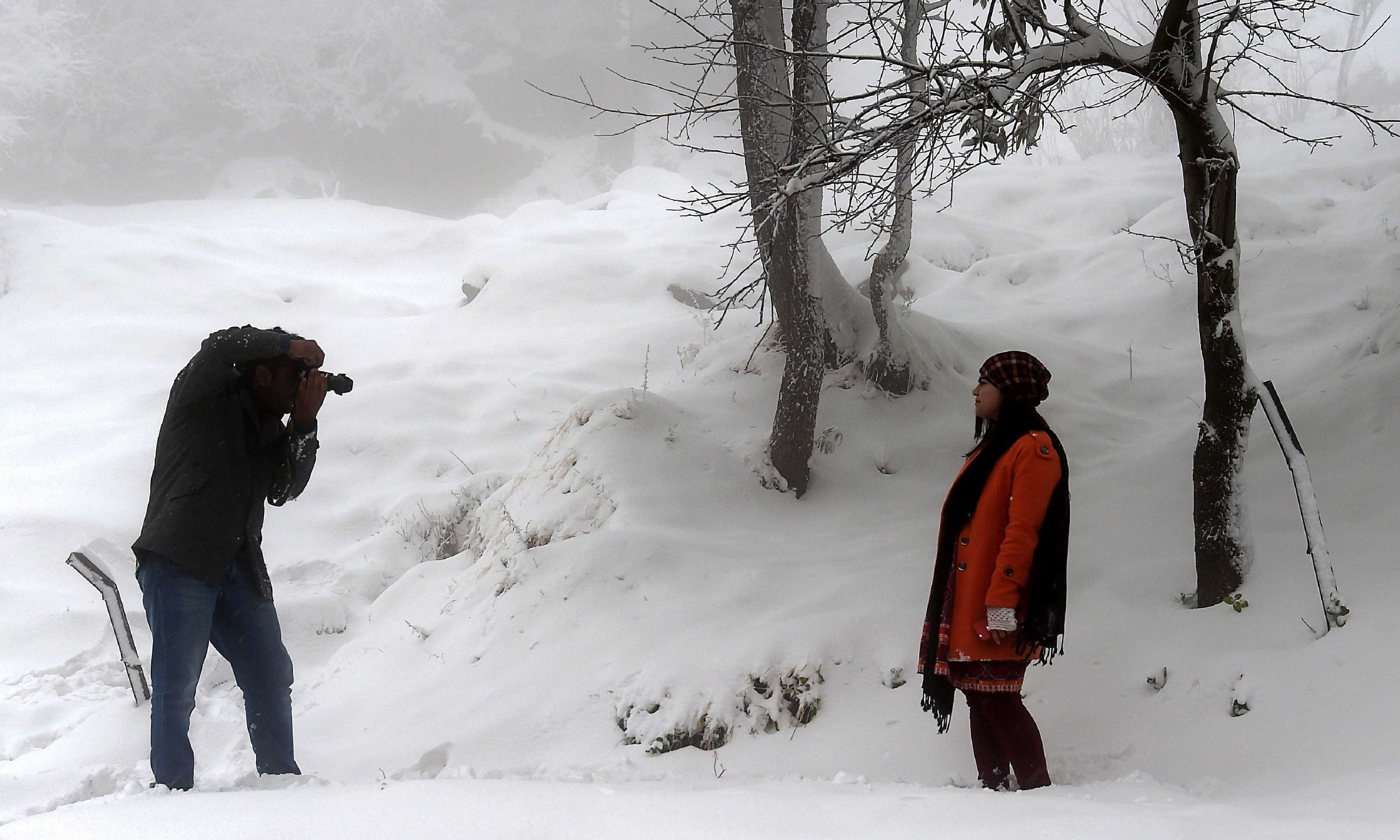 A man takes pictures of a woman as snow falls in Murree. —AFP