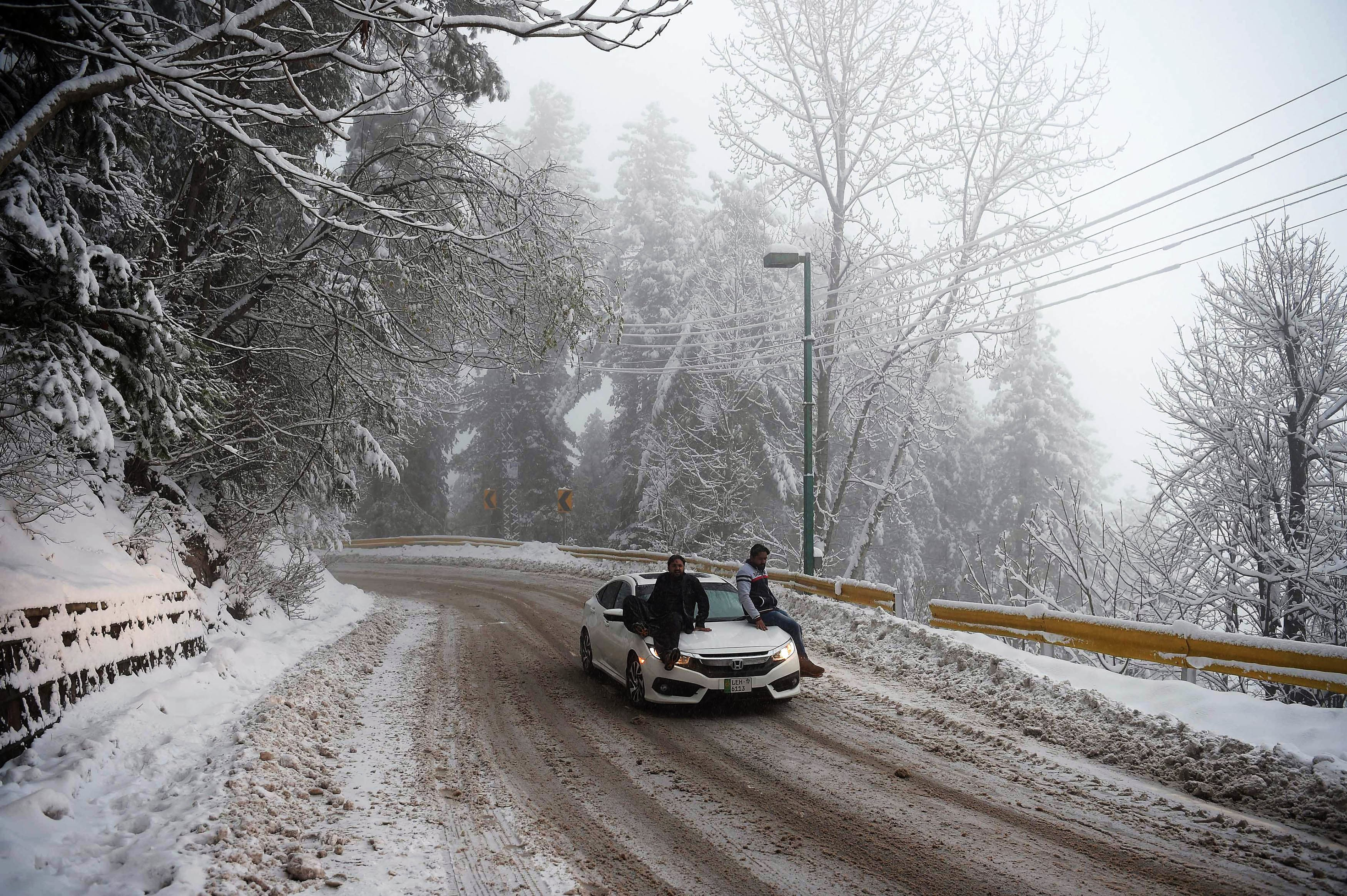 Pakistani tourists sit over a car as they cross a street covered with snow during a snowfall in Murree, some 65 km north of Islamabad, on January 5, 2019. (Photo by AAMIR QURESHI / AFP) — AFP or licensors