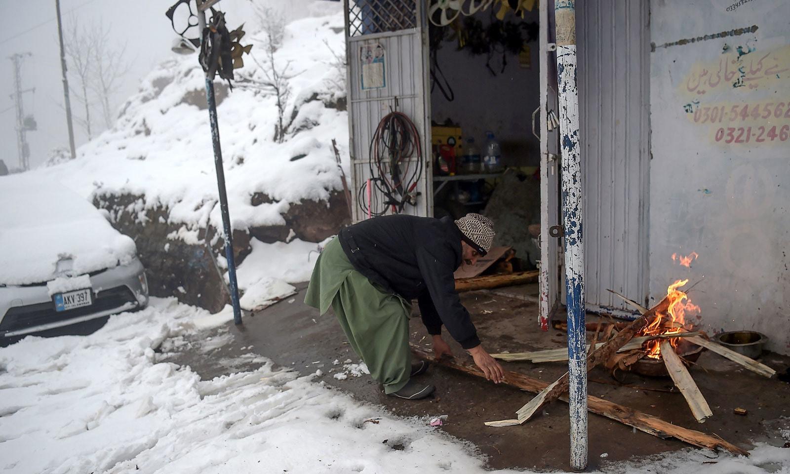 مری میں برفباری کے دوران ایک شخص اپنی ورکشاپ کے باہر لکڑیوں سے آگ جلا رہا ہے — فوٹو: اے ایف پی