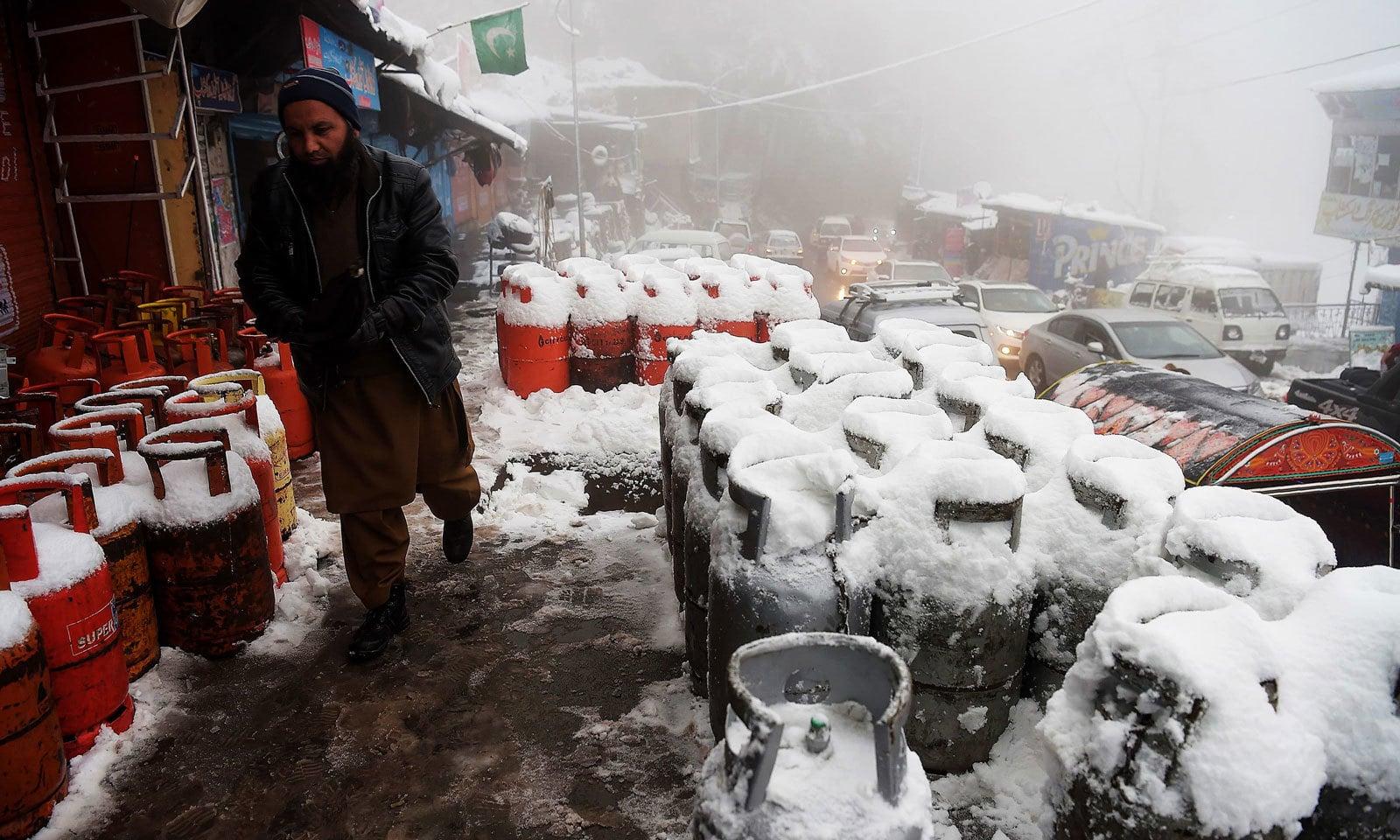 مری میں ایک شخص گیس کے سلنڈرز کے پاس سے گزر رہا ہے جو برف سے ڈھکے نظر آرہے ہیں — فوٹو: اے ایف پی