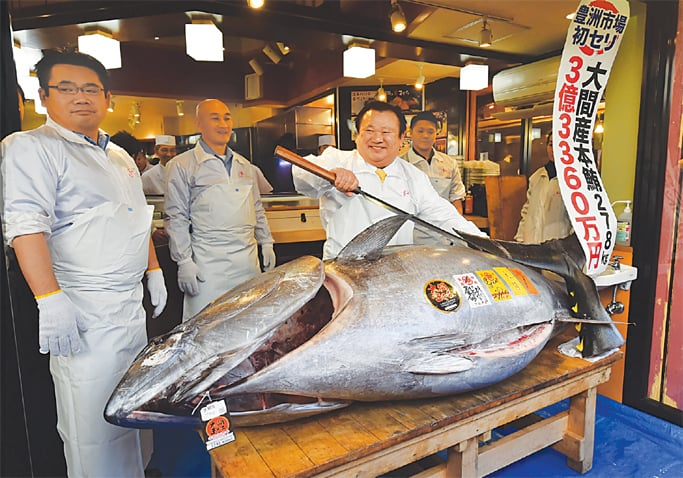 TOKYO: Kiyoshi Kimura (right) displays the 278kg-bluefin-tuna, for which he paid a record $3.1 million, at his restaurant on Saturday.—AFP