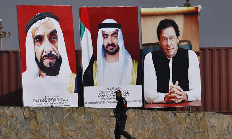 A police commando walks past the huge billboards showing the portraits of Abu Dhabi Crown Prince Sheikh Mohammed, centre, former President of the United Arab Emirates Sheikh Zayed bin Sultan Al Nahyan, left, and Prime Minister Imran Khan to welcome the crown prince to Islamabad. — AP