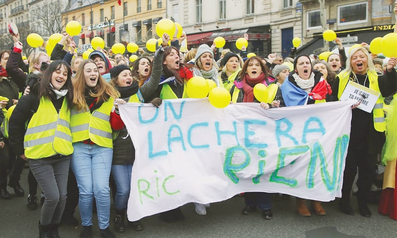 PARIS: Women wearing yellow vests and holding yellow balloons march during a demonstration on Sunday.—AP