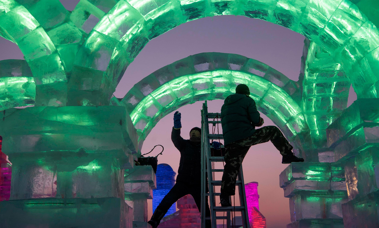 مجسمہ ساز برف کے ٹکڑے نصب کرنے کے بعد انہیں تراش کر حتمی شکل دے رہے ہیں—فوٹو:اے ایف پی
