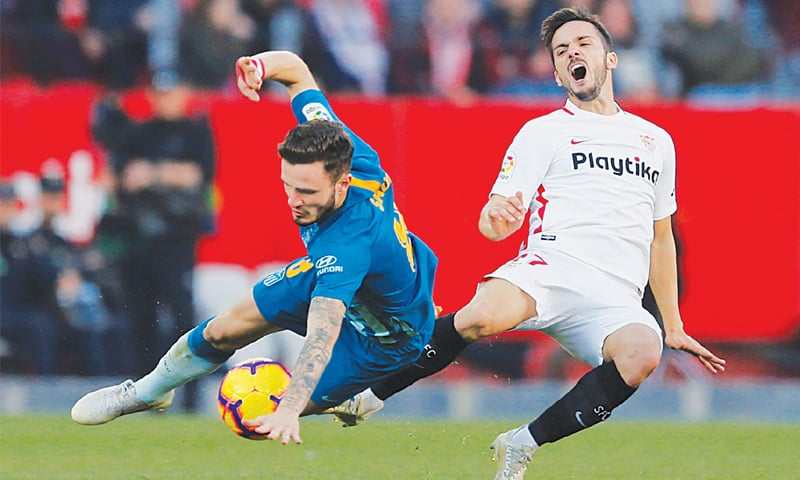 SEVILLE: Atletico Madrid's Saul Niguez fights for the ball with Sevilla's Pablo Sarabia during their La Liga match at the Ramon Sanchez Pizjuan.—Reuters