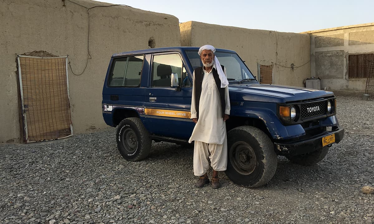 Haji Muhammad Bukhsh stands in front of his car given to him by an Arab prince in Kharan district, Balochistan   Subuk Hasnain