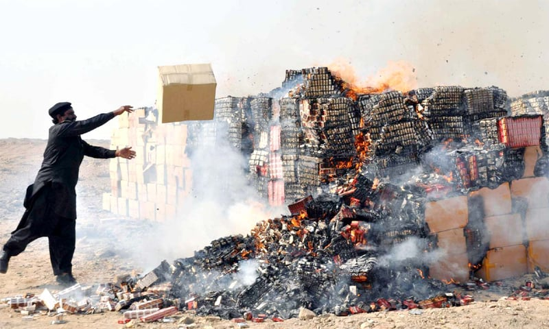 A Customs official burns smuggled cigarettes and other contraband outside Hyderabad on Wednesday. The FBR plans a larger crackdown on smuggled cigarettes around the country.—PPI