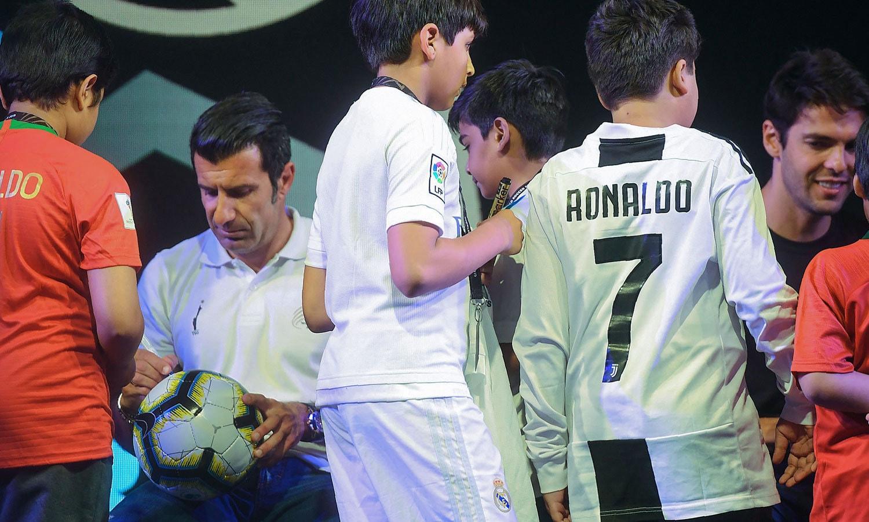 پرتگاک کے لوئس فیگو بچوں کو فٹبال ہر آٹو گراف دے رہے ہیں— فوٹو: اے ایف پی