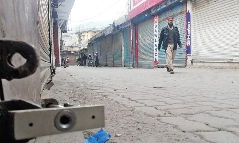 A man walks past a deserted market in Muzaffarabad amid a complete shutter down strike on Thursday. — Dawn