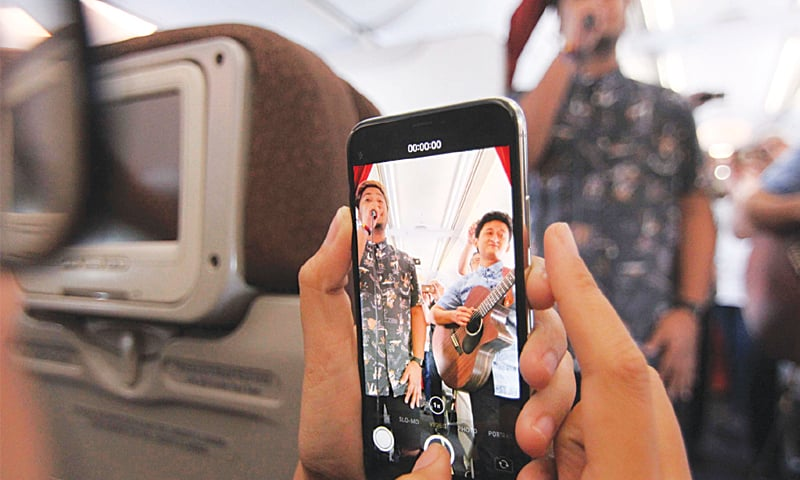 JAKARTA: A passenger using his mobile phone to record a performance by musicians aboard a flight from Jakarta to Bali.—AFP