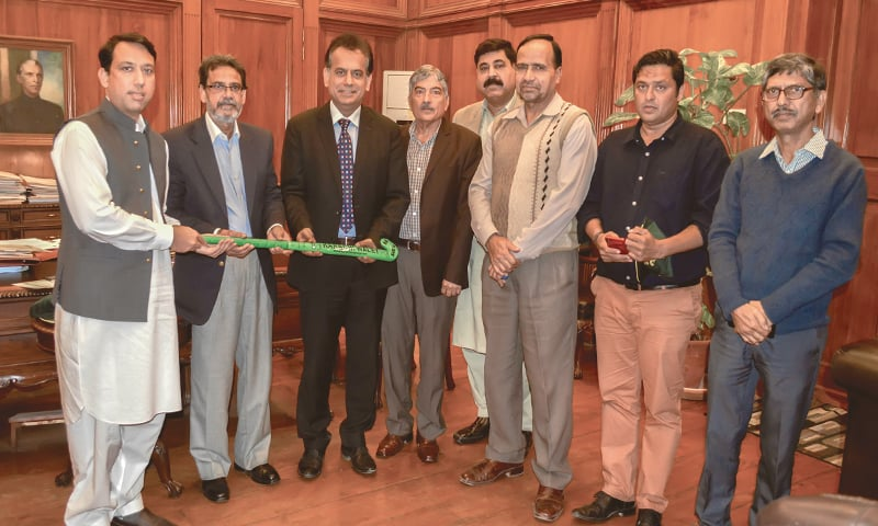FORMER Olympian Hanif Khan (second L) presents a hockey stick to Karachi Commissioner at his office on Friday as DC South and KHA officials look on.