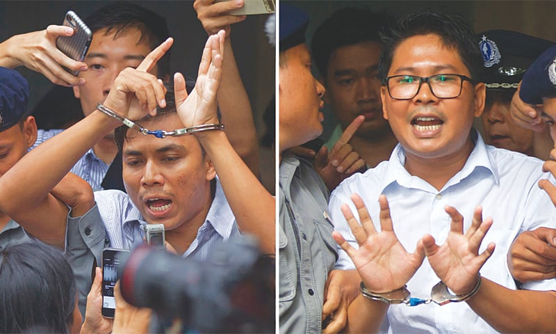 This picture taken on Sept 3 last year shows Kyaw Soe Oo (left) and Wa Lone in handcuffs as they are being escorted by police out of a court in Yangon.—AP
