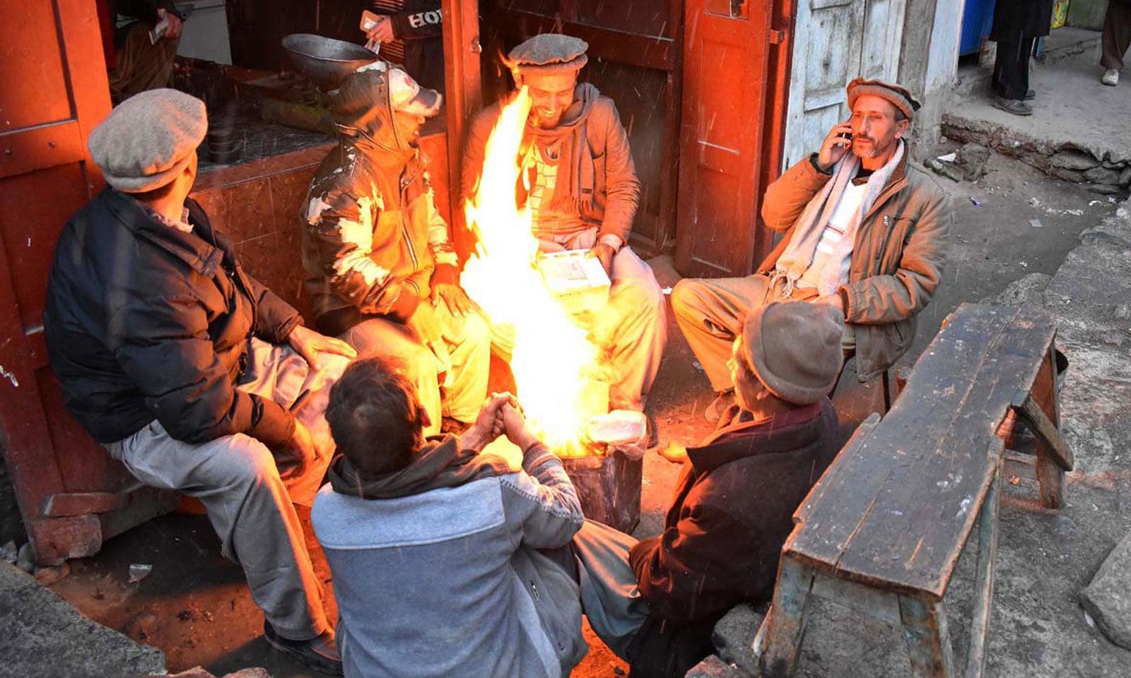 گلگت شہر میں دکاندار برف باری کے بعد ٹھنڈے موسم کا لطف اٹھا رہے ہیں — فوٹو: اے پی پی