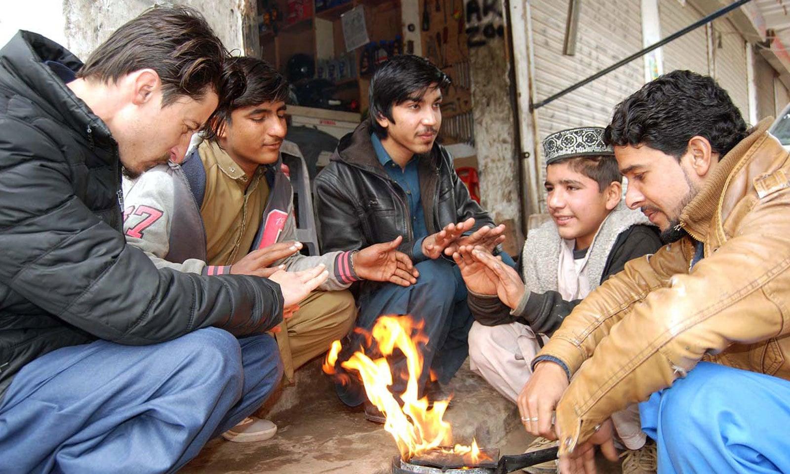اسلام آباد میں نوجوان ٹھنڈے موسم میں آگ کے گرد بیٹھے ہیں — فوٹو: اے پی پی