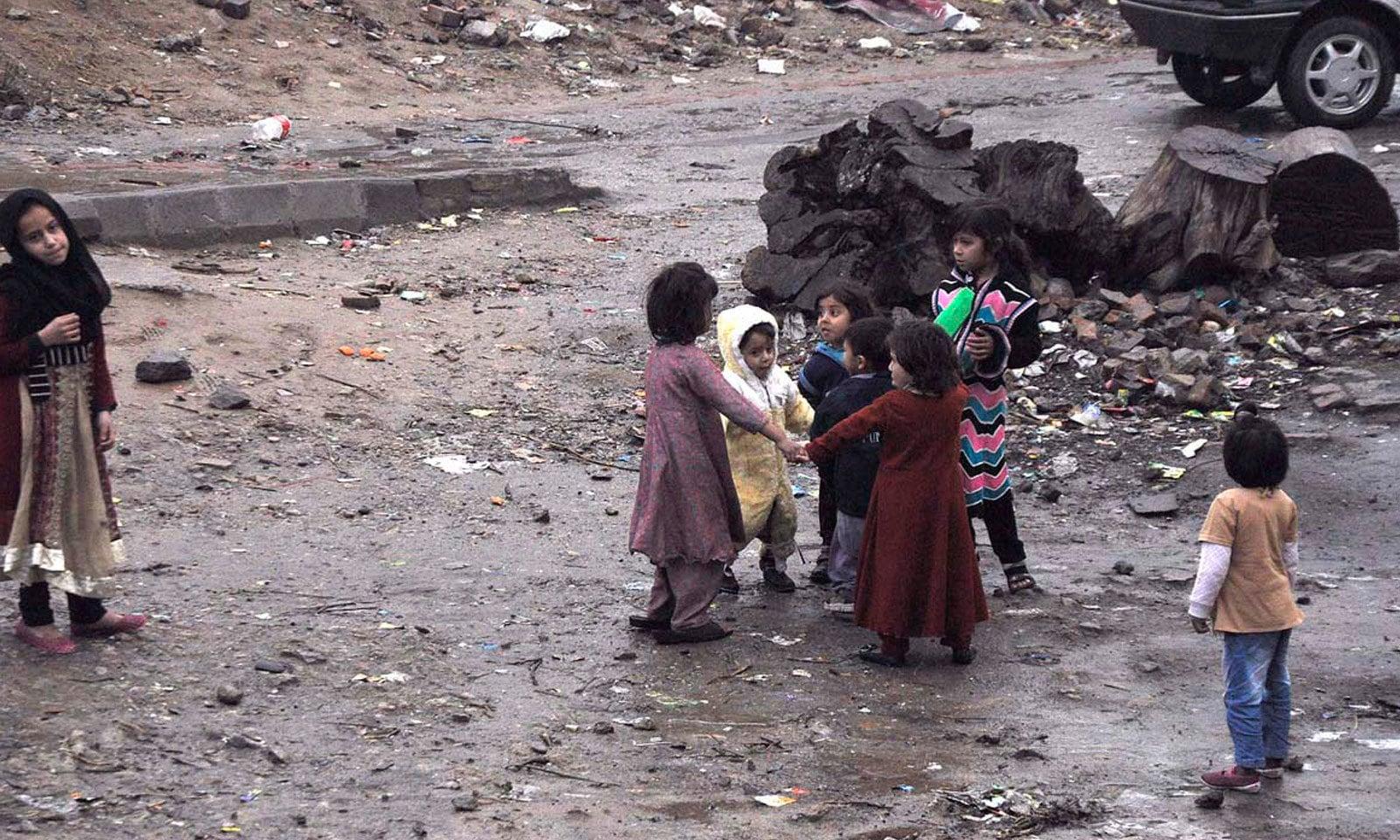 اسلام آباد کے نواحی علاقے میں بچے بارش میں کھیل رہے ہیں — فوٹو: اے پی پی