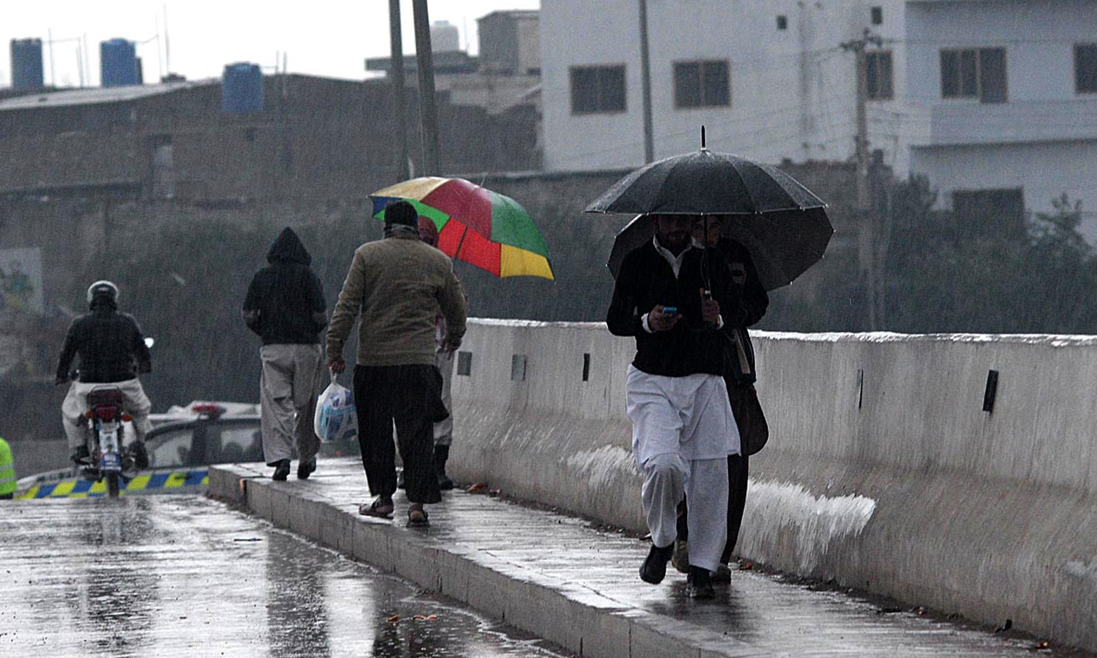 راولپنڈی میں شہری بارش سے بچنے کے لیے چھتریوں کا سہارا لیے ہوئے ہیں — فوٹو: اے پی پی